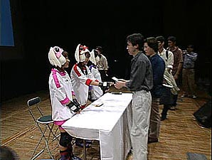 The three voice actors in cosplay outfits greet fans behind a table.