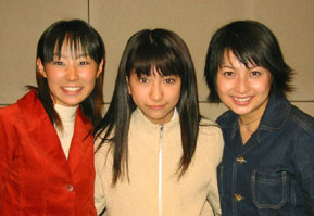 The three voice actors in casual clothing together and smiling.